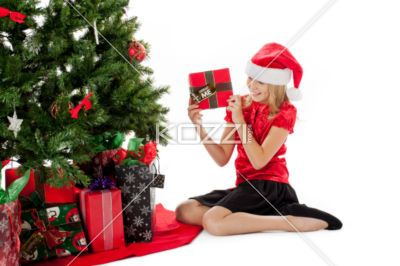 smiling young girl holding her chistmas gift. - View of a smiling young girl holding her chistmas gift, Model: Shania Chapman - Agent is Breann at MMG. breann@nymmg.com