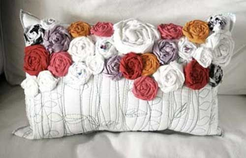 This creative accent pillow is decorated with fabric flowers and free motion…