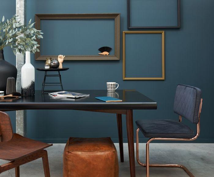 De matte grijs blauwe muur geeft de schilderijlijsten in bruin
