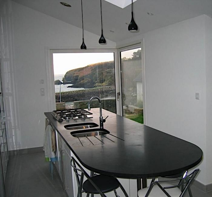 Beautiful central kitchen island with rounded black granite honed