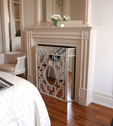 Faux fireplace for TV with mirrored fireplace screen. Cool idea ...