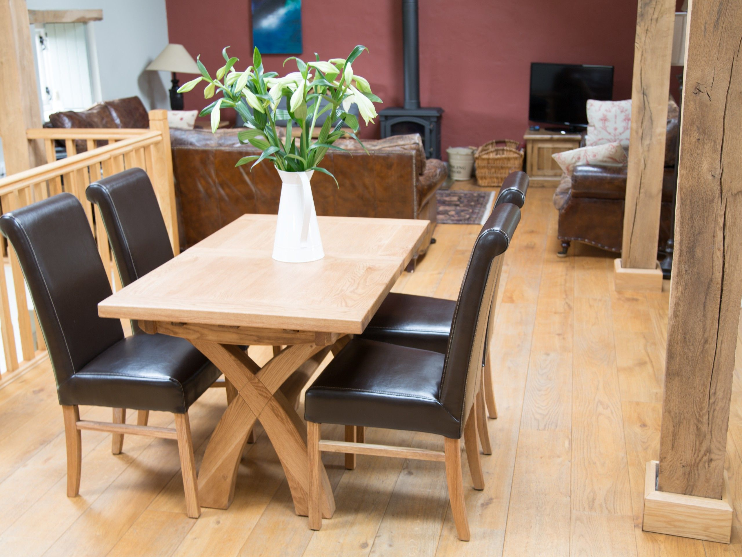 Cross leg oak dining table and leather dining chairs in a barn ...