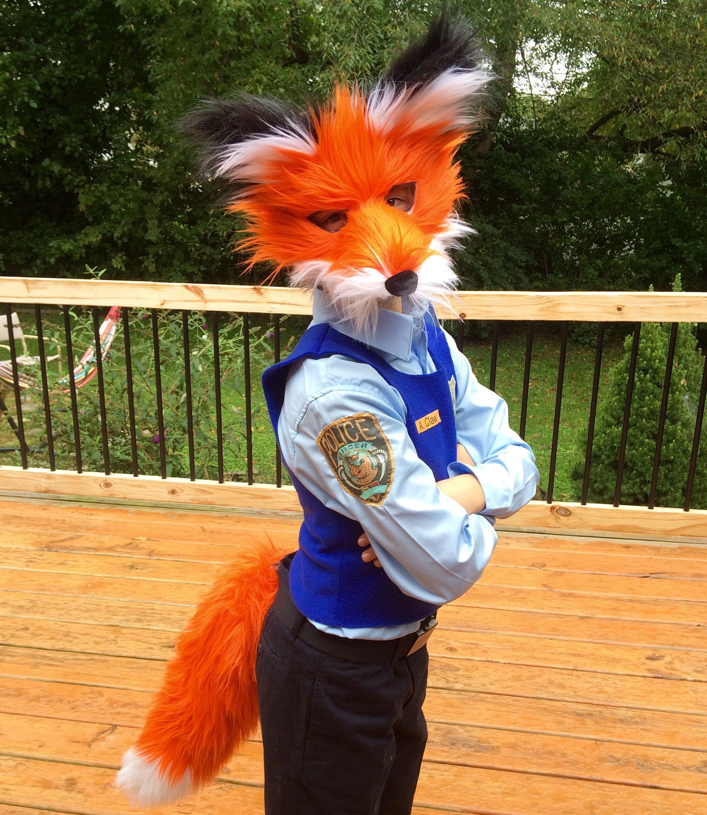Zootopia Nick Wild Halloween costume with diy police costume, fox tail, and fox mask.