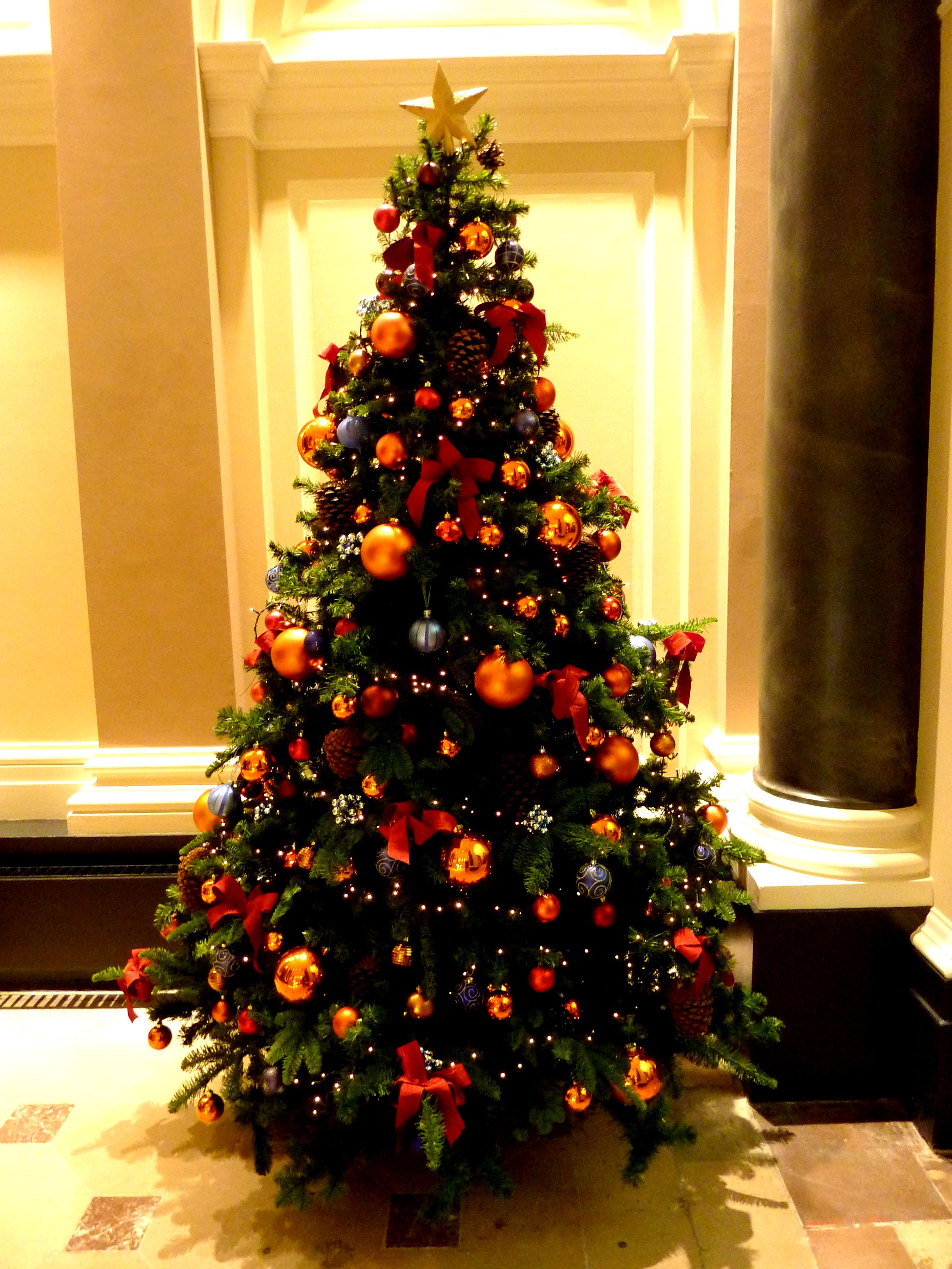 a sweet tree with blue orange and red ornaments and bows - Orange Christmas Tree