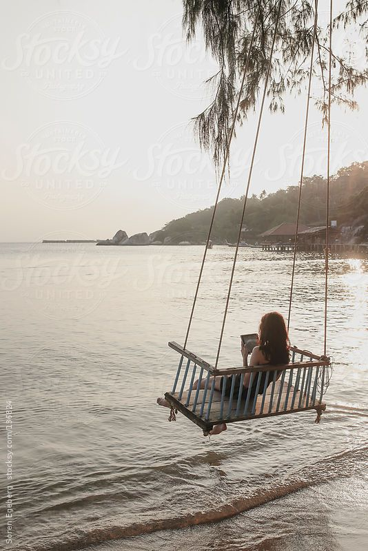 Young girl using tablet computer in seated rope swing over for Swing over water