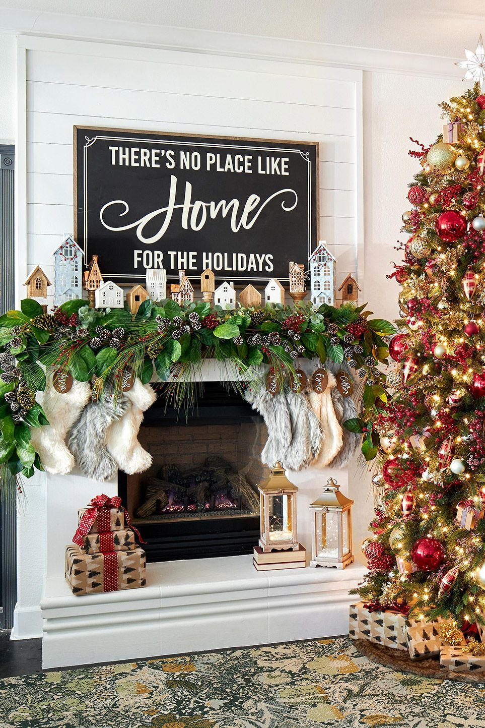 Draw attention to your mantel display with an oversized sign. To complete the look, a collection of small houses peek out above a lush Christmas mantel garland with eucalyptus, pinecones, and small berries. #christmasmantel #christmasmantelideas #manteldecorations #garland #holidaydecor #bhg