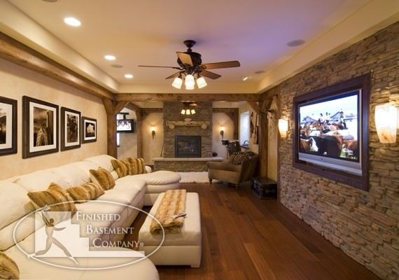 parede de pedra, detalhes de madeira pela parede, luzes ao lado da TV