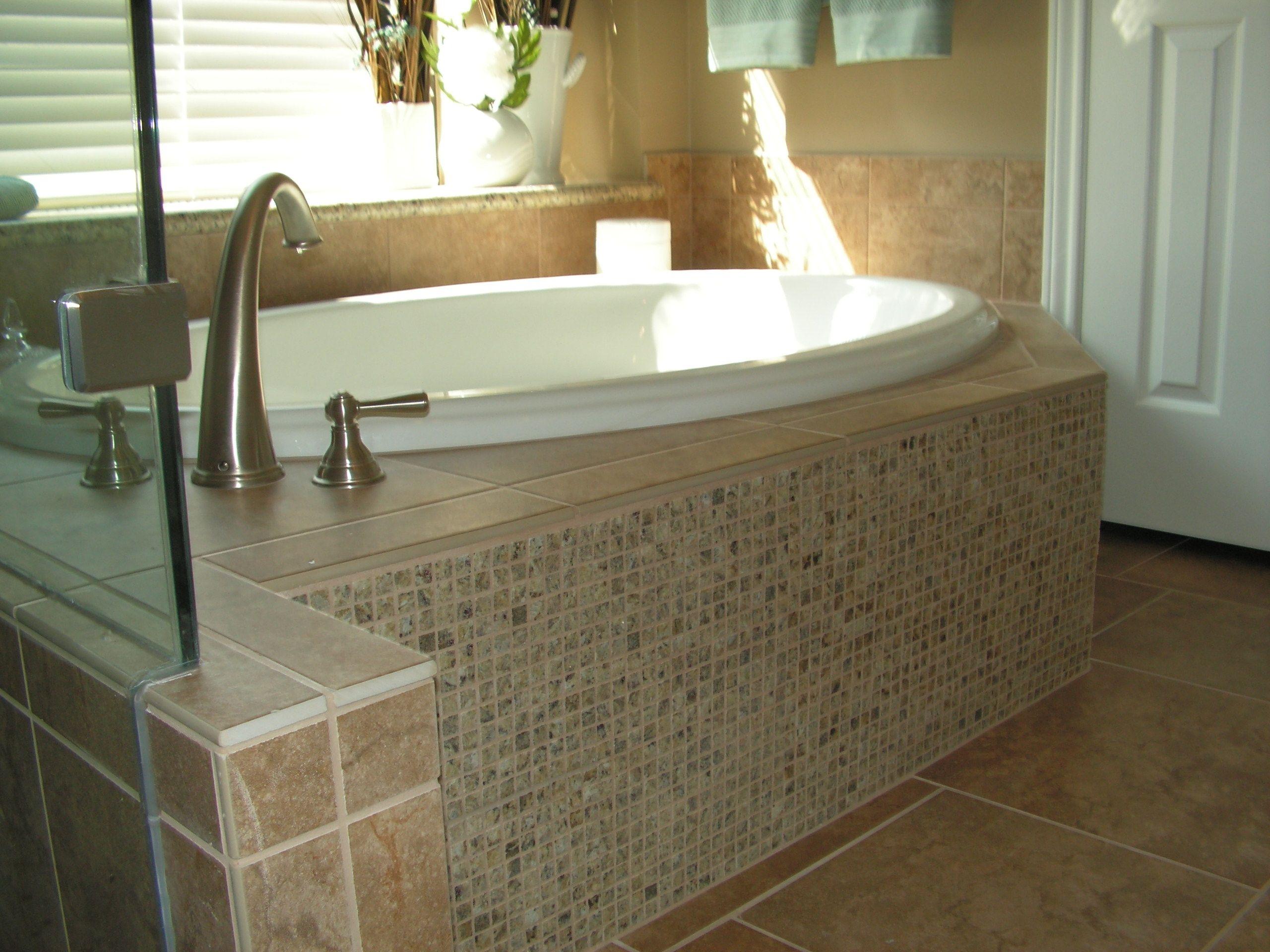 master bath with granite mosaic tub skirt to match granite vanity