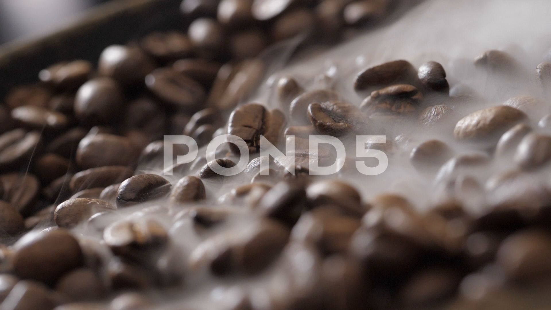Coffee beans rotate while roasting. Smoke comes from