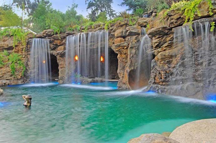 a luxurious pool with a waterfall and a cave at old lion manor california