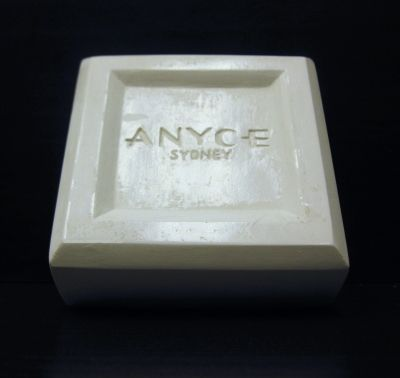 "Anyce Sydney Soap Bar Plaster Prototype. Square soap bar with bevelled edges and inset surface with engraved lettering. 2.5625"" x 2.5625"" x 1"" thick. Company located in North South Wales, Australia."