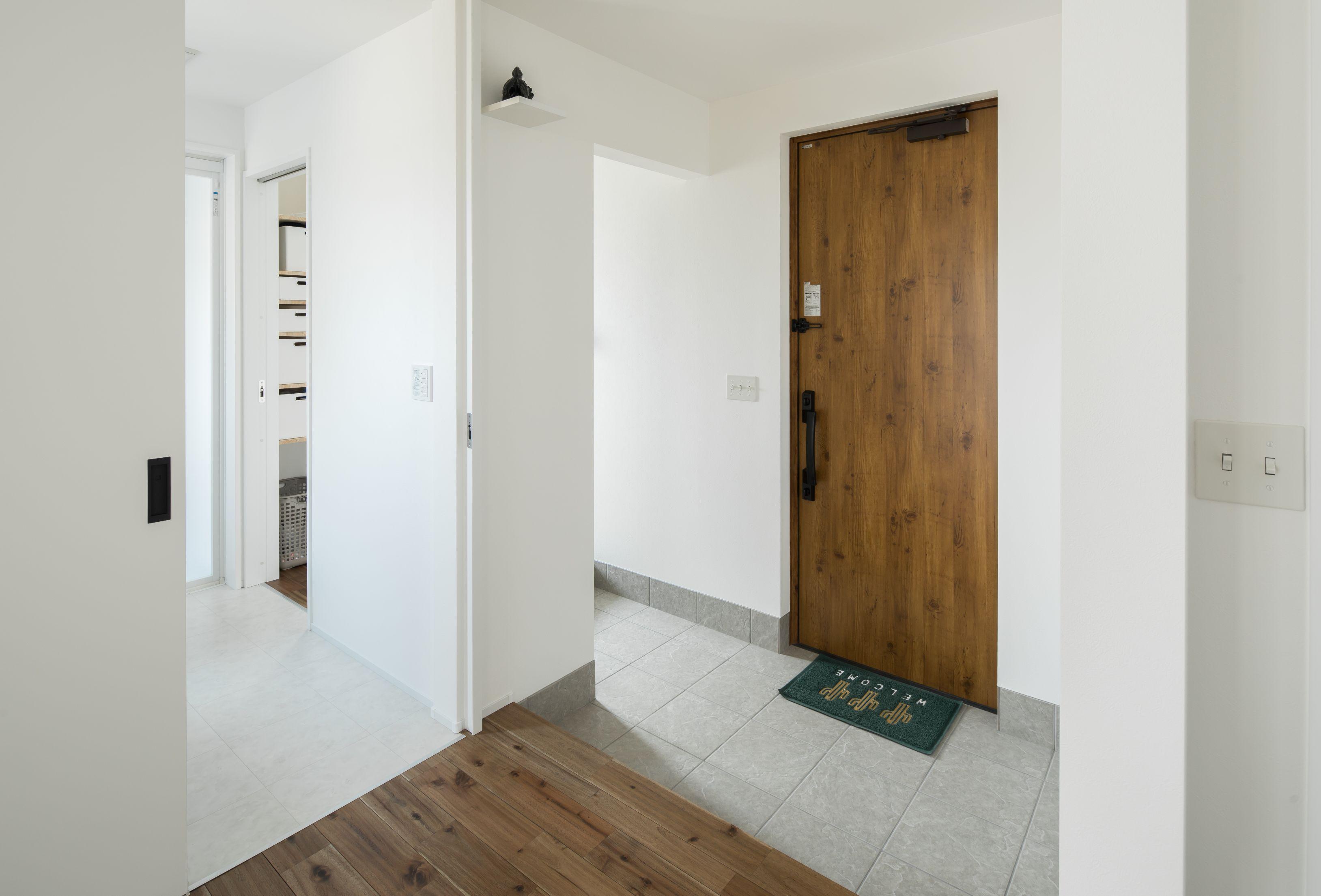 表情のある木目ドアと薄いグレーのタイルは 白との相性ぴったり