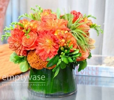 """The enthusiastic Orange Sunrise is an inspiring arrangement designed with Roses, Coxcomb, Mini Cymbidium Orchids, Freesia and Air Plants. The tapered 6"""" x 6"""" circular glass vase is lined with fresh green leaves. The arrangements overall height is 12"""" x 12"""". It will surely cultivate fun and expressions of joy! $139.00"""