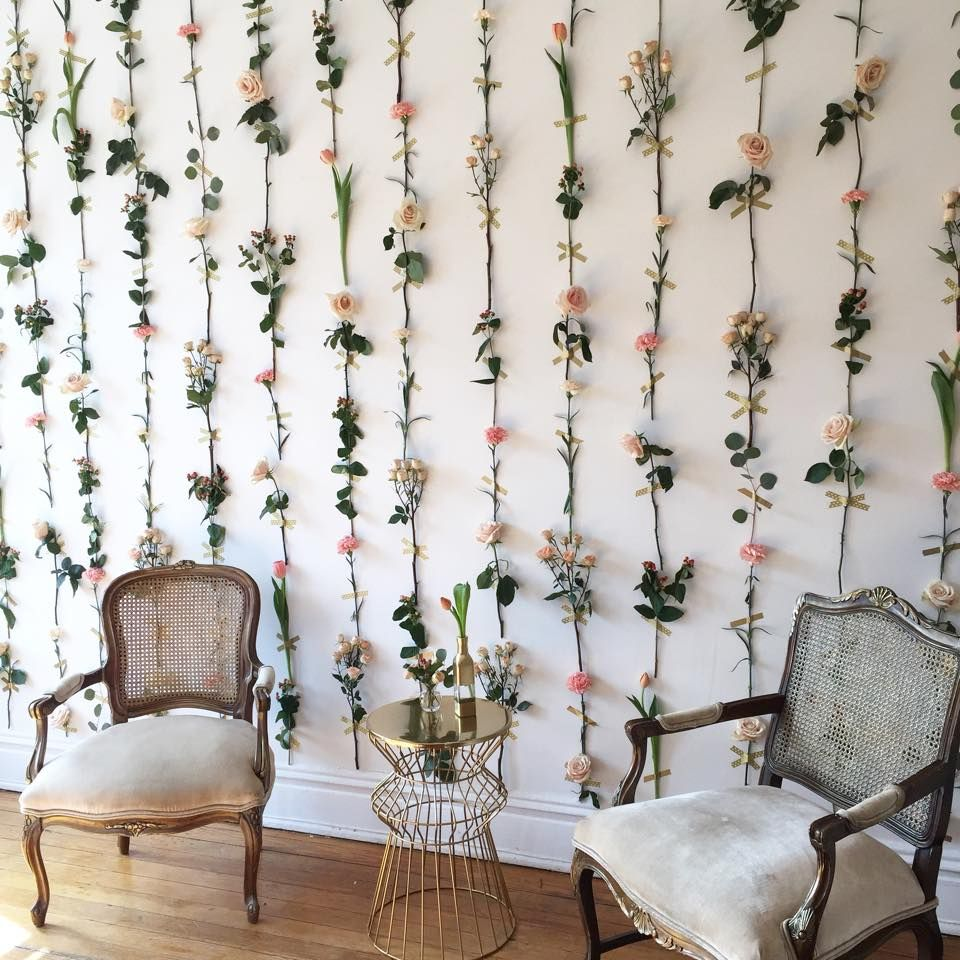 a flower wall (with fake flowers) with exposed tape across