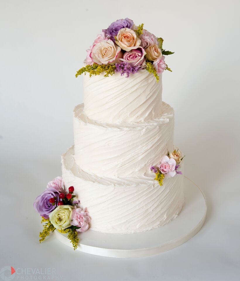 Diagonal texture buttercream wedding cake with fresh flowers. A ...