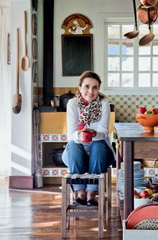 """A cozinha completamente integrada ao estar, com direito a um fogão a lenha no canto, foi uma exigência de Andrea, que adora subir a serra acompanhada de amigos e muito vinho. """"Luz, gente e bons papos são essenciais aqui"""", brinca ela."""