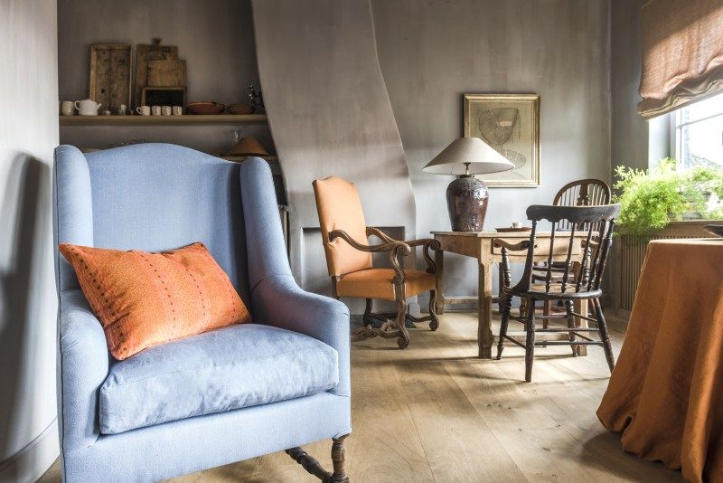 Belgian style interior with blue wing chair, wood floors, and pumpkin orange accents in an elegant rustic Bruges guesthouse apartment (called White Rooms) with professional interior design by Natalie Haegeman of NH Interiors. NH Katelijne
