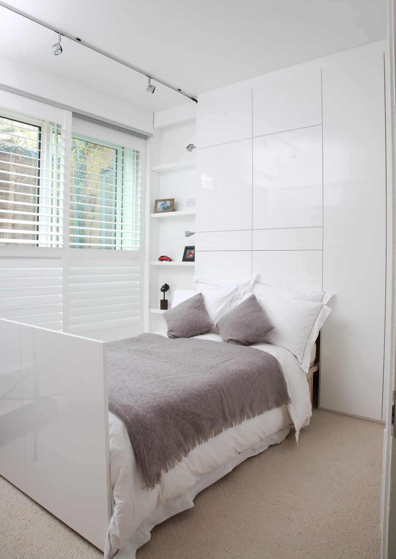 A modern spare bedroom and study with an electrically retracting