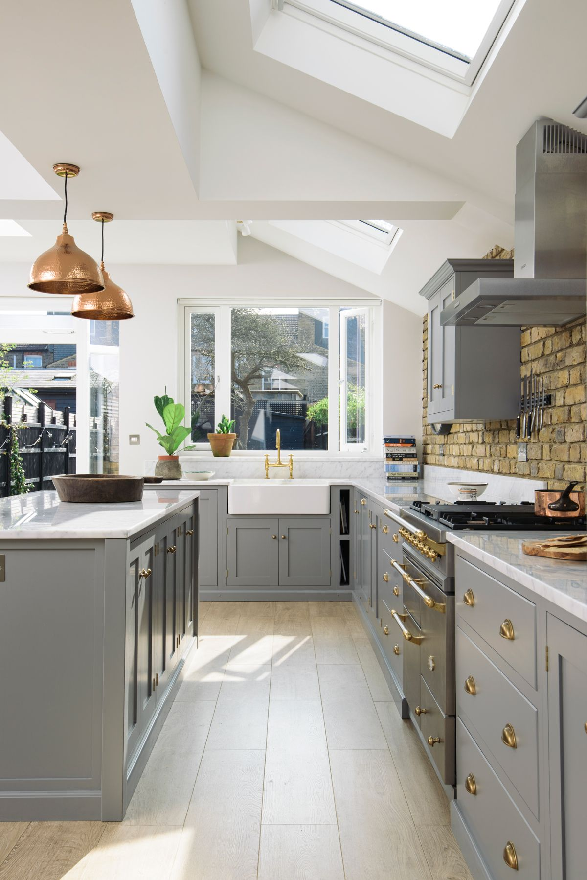 This wonderful kitchen extension in South London was filled with sunshine and style; grey cupboards with brass details and Carrara marble worktops