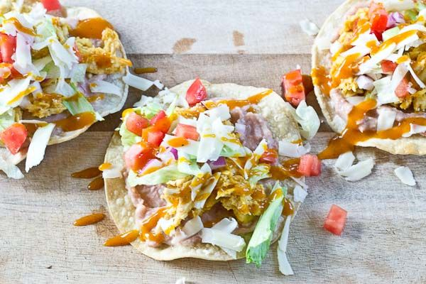 Slow Cooker BBQ Chicken Tostadas-- pulled chicken breast cooked with Trader Joe's famous Carolina Gold BBQ Sauce topped on crispy baked tostadas and veggies. This weeknight dinner will quickly become a family favorite. High protein and gluten-free.| @KristinaLaRueRD | loveandzest.com