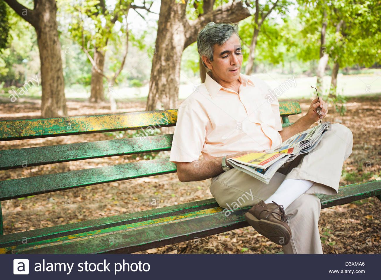 Man Sitting On A Park Bench And Reading A Newspaper Lodi Gardens Man Sitting Lodi Park Bench
