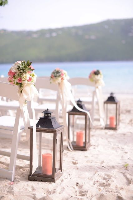 Beautiful wooden lanterns with coral pillar candles lining the ...