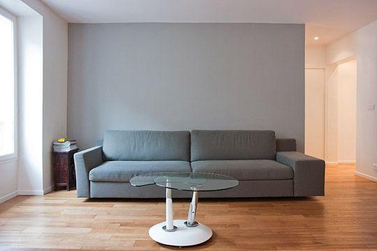 Un large canapé gris se trouve contre un mur peint en \