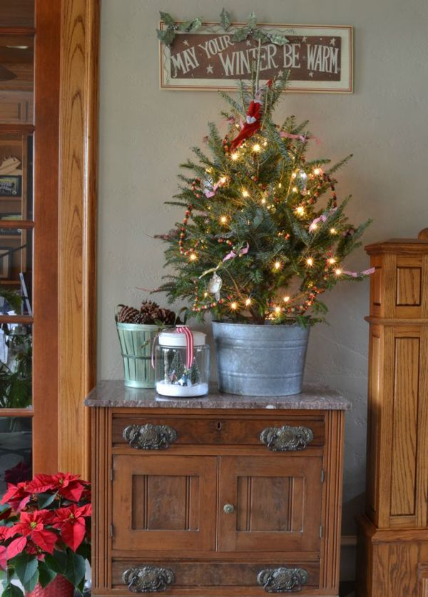 Galvanized tub with tree and bushel basket with winter pine cones