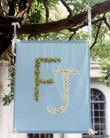 Silk flowers spell out a couple's initials on a silk faille banner.