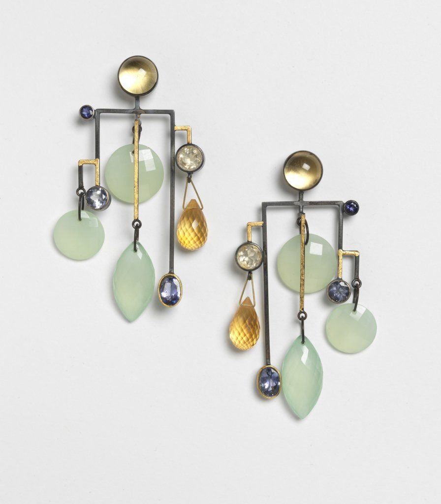 "SUZAN REZAC IRIS  Earrings. Oxidized silver, 18K gold, gold leaf, aqua chalcedony, citrines, iolite, tanzanite  3/8"" x 1 3/4"" x 2 1/2""  Through the years, Suzan Rezac has collected scores of gem stones. Each stone is beautiful in its uniqueness, but dazzlingly rich when grouped with others. A superb colorist, Rezac painstakingly combines, recombines, and separates stones until each piece exudes a harmonic balance of color, shape and size."