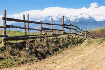 rural landscape in spring composite landscape of mountain ridge in the distance with snow capped tops and fields with fence along the country dirt road warm sunny weather...