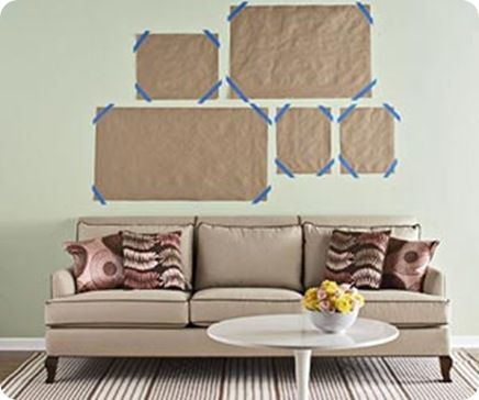 A tried and true picture hanging method. Cut scrap paper to the size of the frame and mark the nail location on the paper. Using painter's tape, move the paper templates around the wall until satisfied. Then hammer the nail through the marks. Remove the paper template and hang!
