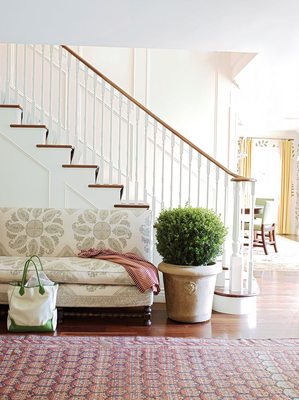 In the entryway, an  aged English planter sits beside a love seat upholstered in a Samarkand fabric by Peter Dunham Textiles. PHOTO: Victori...