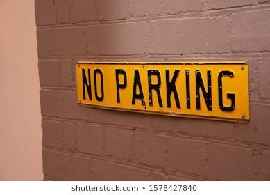 A Square Yellow vintage no parking sign on grey brick wall love sy