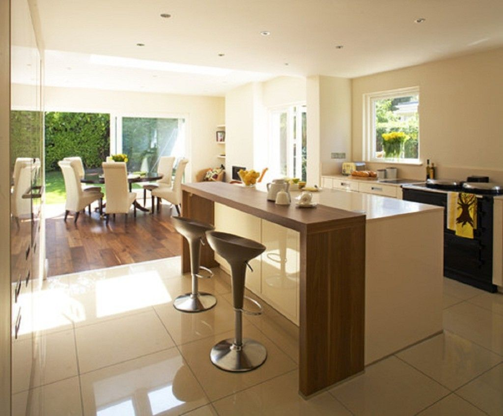 Stylish wooden kitchen bar table near stainless steel barstools near