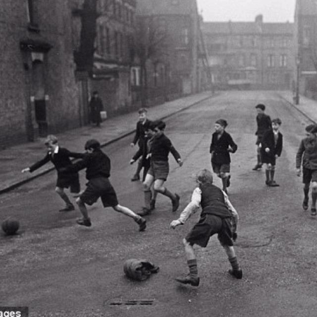 eb7387c784c4 Boys playing football in the road without a care in the world... Those were  the days.