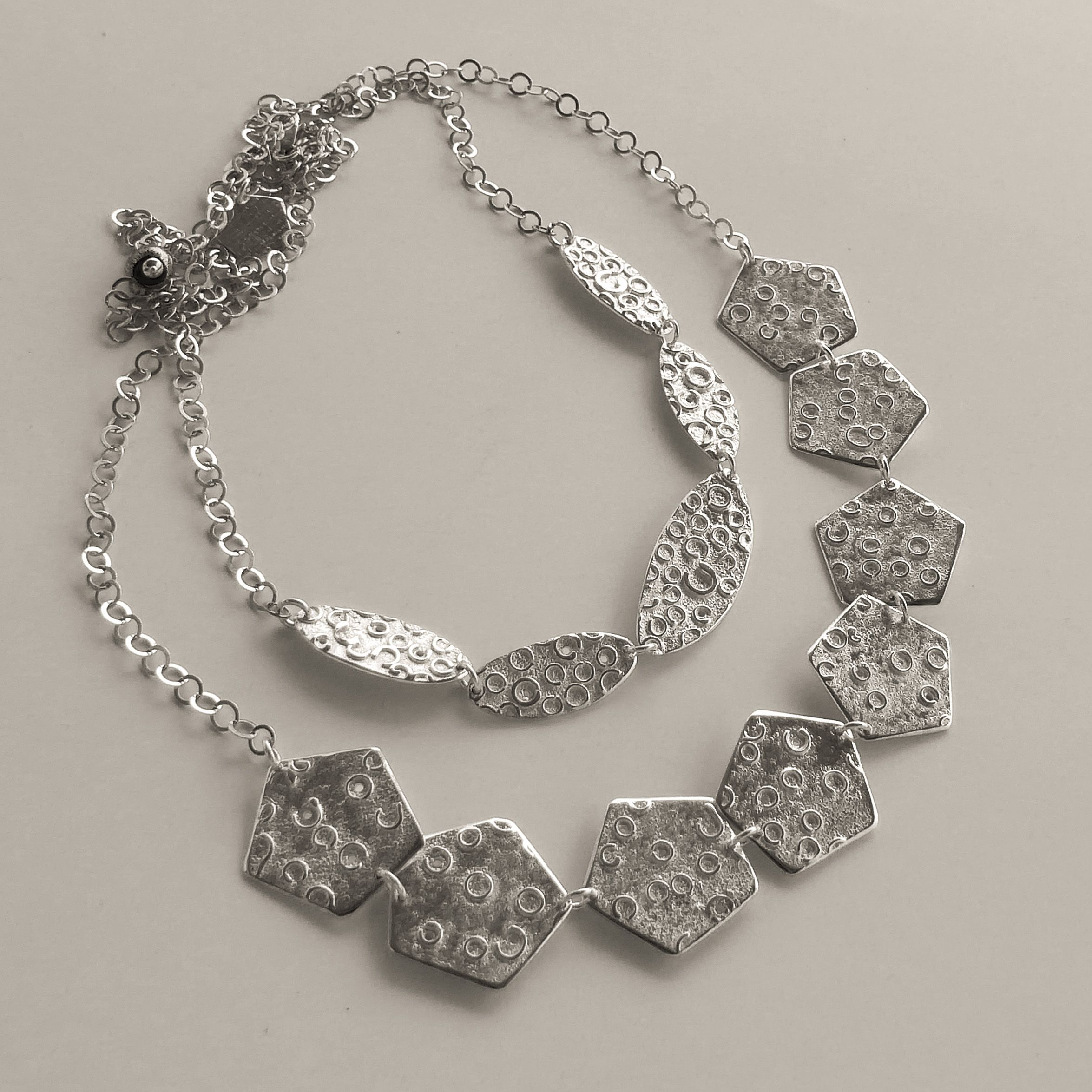 Pentagon and Oval necklaces from the Dandelion series . #jewellery #contemporaryjewellery #silvernecklace #jewelery #contemporarycraft #handmadejewellery #flowerjewellery #glosguild