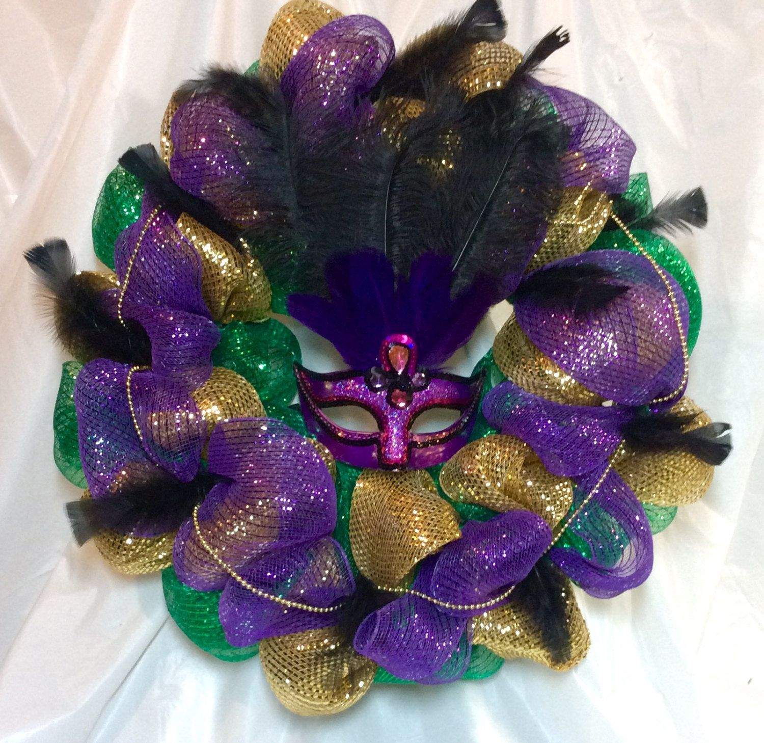 """Mardi Gras wreath. Temptation fuscia mask w/purple, black feathers. Gold, purple, green mesh. Gold beads, black feather accent. 21"""" wreath. by KhQualityCreations on Etsy"""