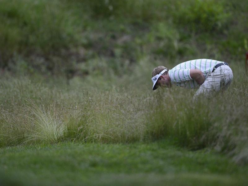 US-Golfer Russell Henley ist bei den US Open im hohen Gras am 17. Loch auf der Suche nach seinem Ball. (Foto: Erik S. Lesser/dpa)