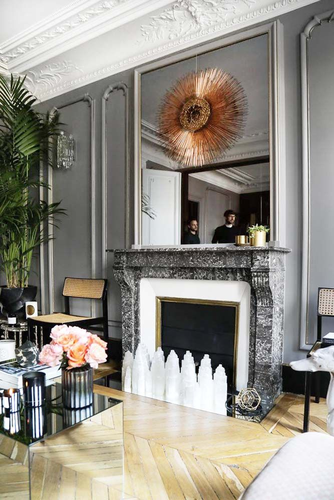 Grey living room in Paris pied-à-terre with sunburst mirror and chevron flooring on Thou Swell @thouswellblog
