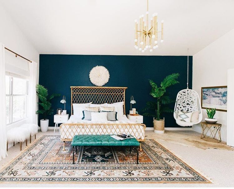 dark blue accent wall, pops of gold and teal, grounded ...