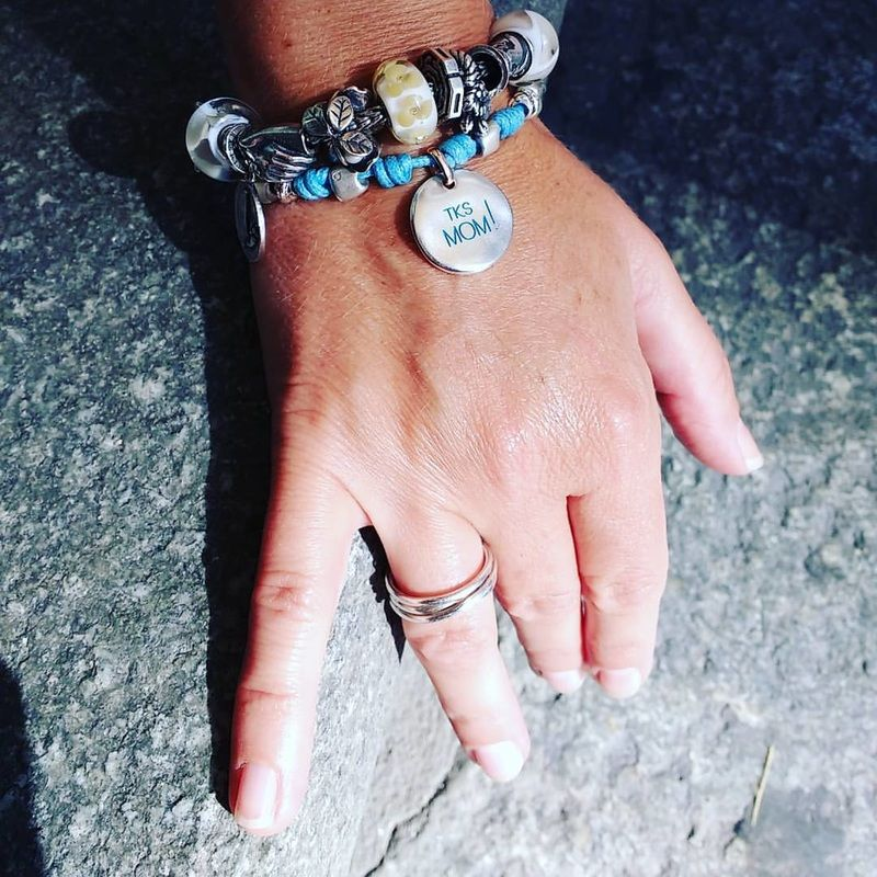 Manuela, volto sorridente e competenza per una delle colonne portanti della Gioielleria Principe, posa oggi per noi indossando l'anello Filodellavita e i bracciali componibili con i beadsTrollbeads, le monete Civita Queriot el'argentodi Giovanni Raspini.