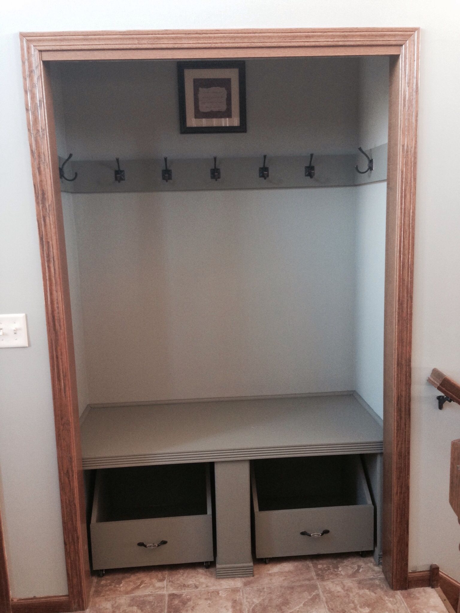 Front door closet with doors removed and shelf hooks and wheeled