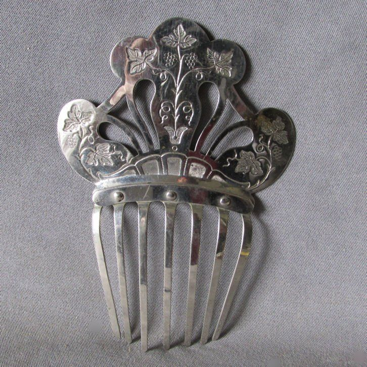 An antique Victorian/Edwardian ladies hair comb. The comb is made of nickel plate steel and features an engraved design of grape vines.