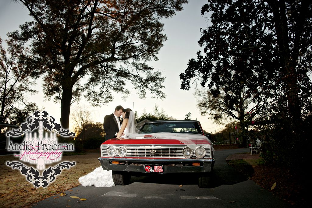 Bride and groom portrait with red vintage car.    Classic fall wedding.  Photography by Andie Freeman Photography www.TheAthensWeddingPhotographer.com Planning and Coordinating by Wildflower Event Services www.WildflowerEventServices.com Venue and Floral:  The Thompson House and Gardens, Athens, GA