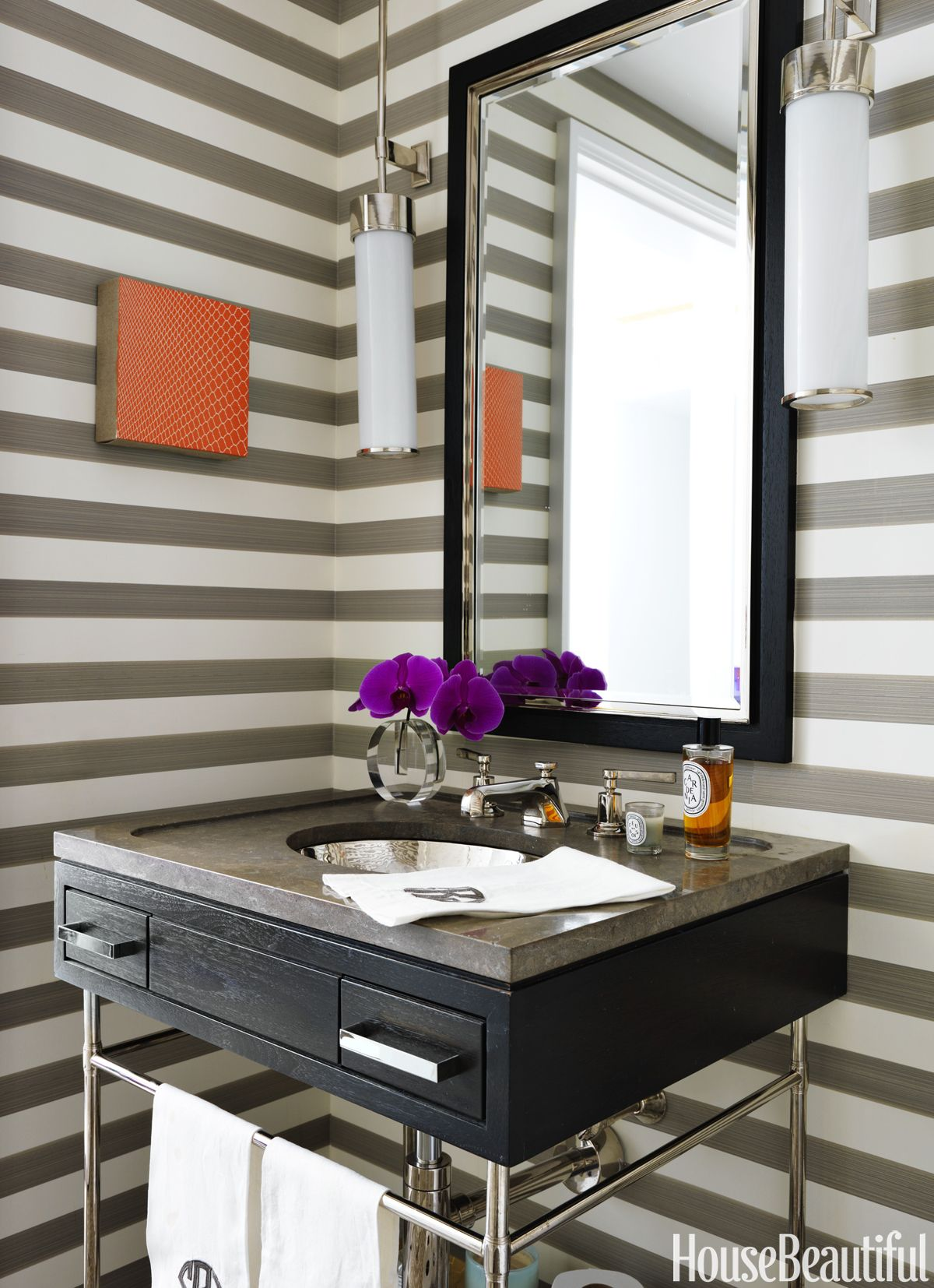 """I'm pretty sure this stripe is supposed to be hung vertically, but I love it this way!"" Sarah Rose says about Farrow & Ball's Five Over Stripe wallpaper. It brings a bold touch to the powder room. A painting by Sara Eichner adds a pop of orange. - HouseBeautiful.com"