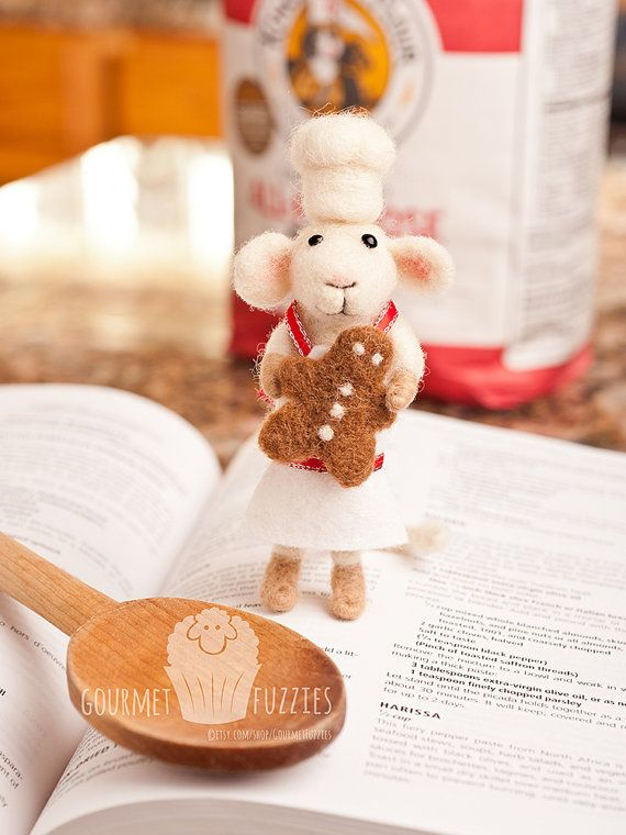Gabriel the Gingerbread Baker - Handcrafted, needle felted collectible. Gabriel comes with a needle felted gingerbread man, needle felted chef's hat and a white wool felt apron with red ribbon trim! He's the perfect addition to your kitchen for the holiday season!