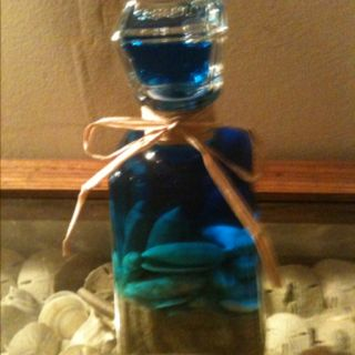 Old bottle filled with sand and olive shells