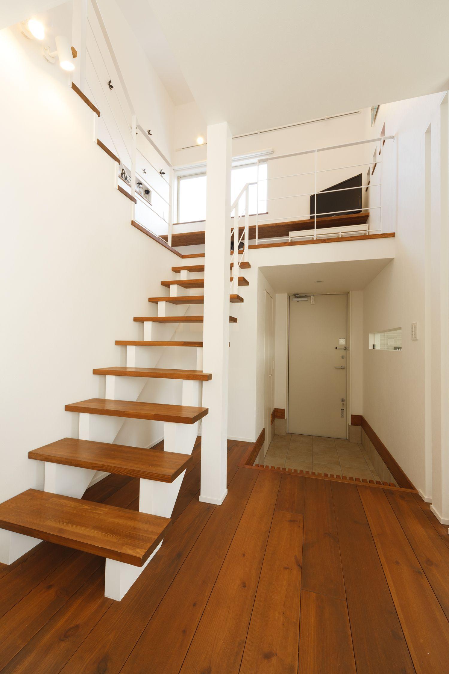 玄関スペースの上部には中二階をプランニング 空間に無駄がありません 中二階 スキップフロア 玄関 エントランス ストリップ階段 シースルー階段 段板 無垢フローリング リクシル 鉄骨手摺 アイアン手摺 柱 デザイン インテリア シンプル ホワイト