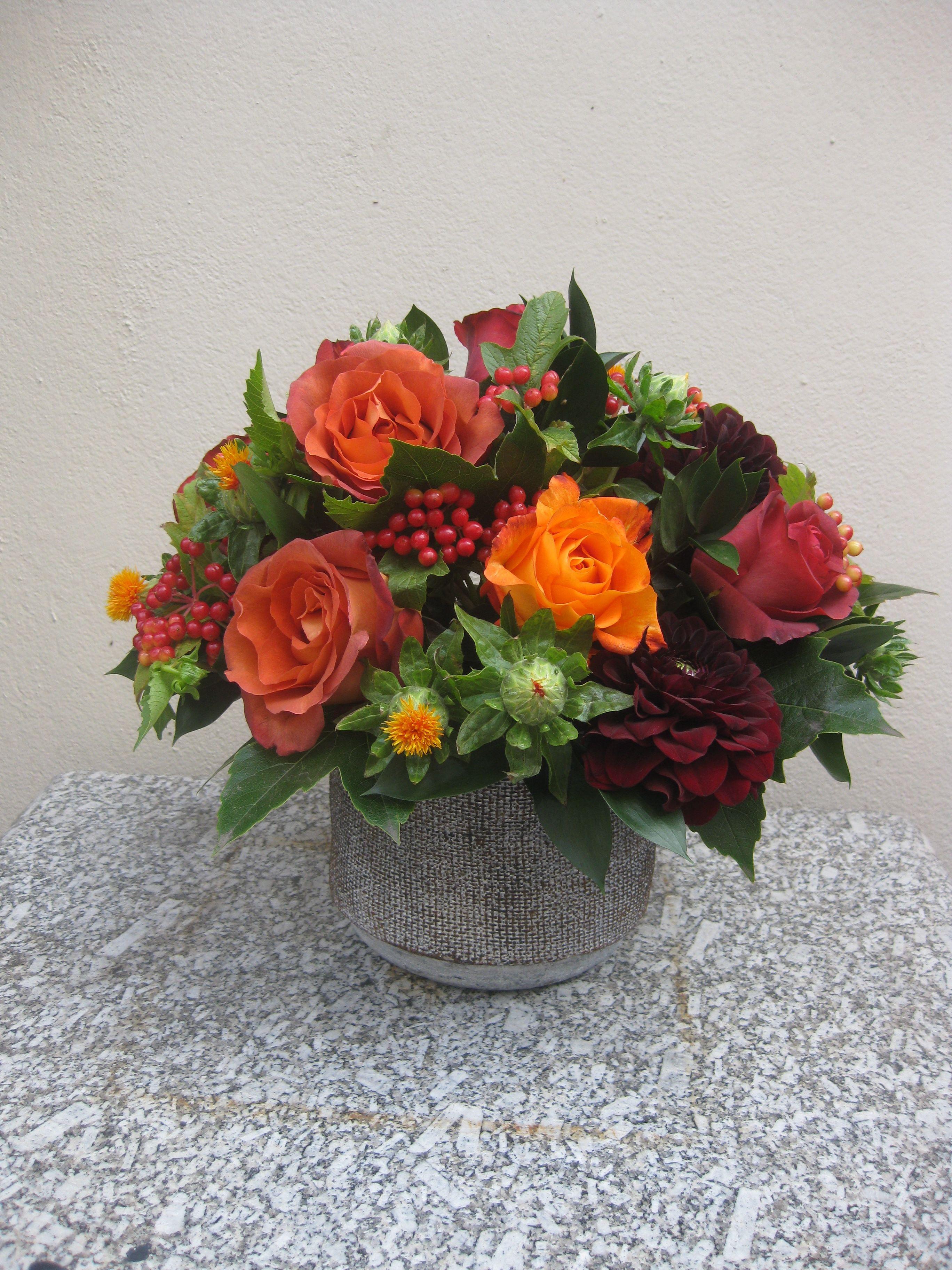 Autumnal flower arrangement of orange roses red dahlias